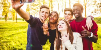 Selfie of a group of multi ethnic teenagers embracing outdoor.