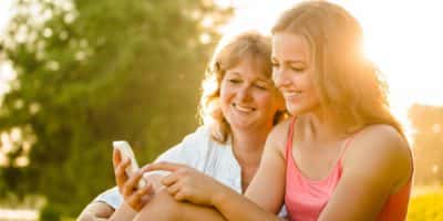 Teenage girl showing her mother photos on mobile phone outdoor in nature with setting sun in background